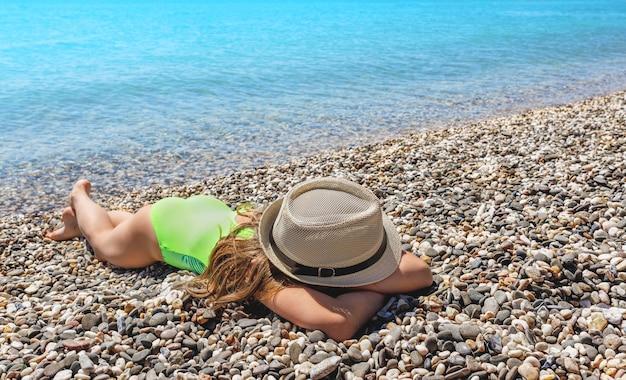 Menina tomando banho de sol no mar azul na praia no verão copie o espaço para o texto