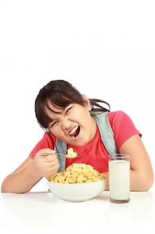 Menina tomando café da manhã com leite isolado no branco