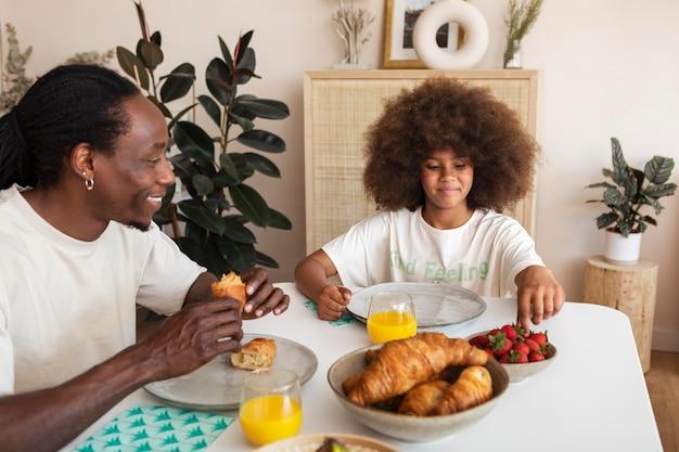 Menina tomando café da manhã com o pai