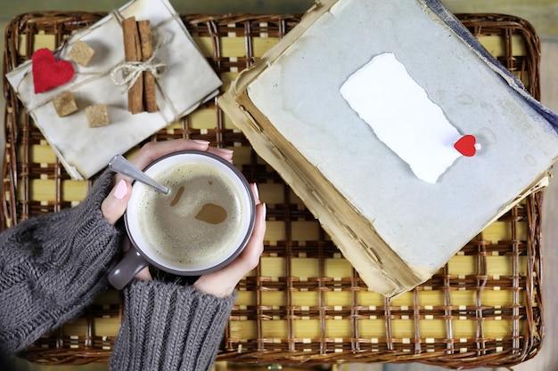 Menina tomando café e olhando para o cartão de dia dos namorados