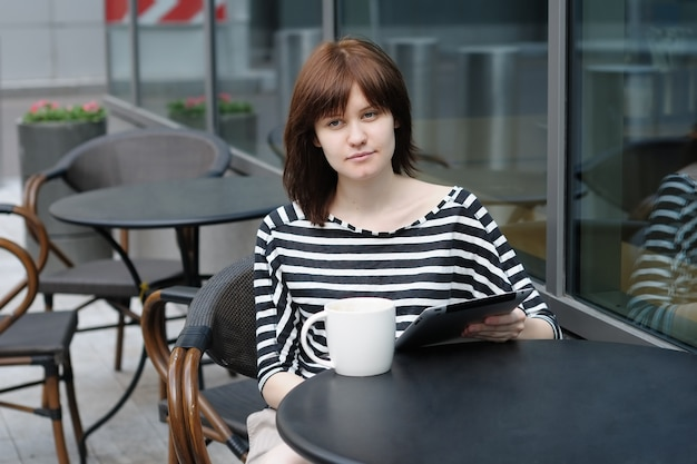Menina tomando café e usando o tablet pc em um café ao ar livre
