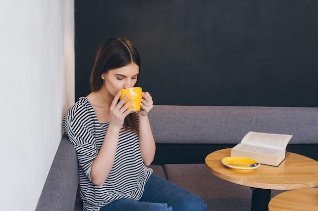 Menina tomando café em uma loja de café