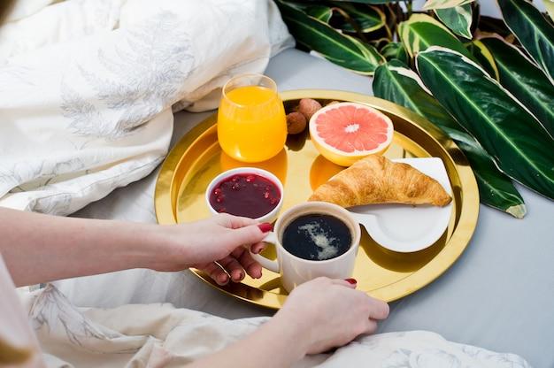 Menina tomando café no café da manhã no quarto, serviço de hotel.