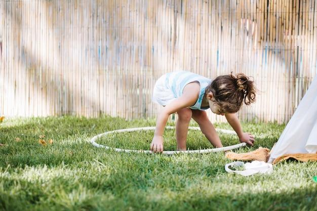 Menina tomando hula hoop do chão