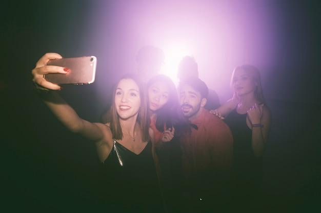Menina tomando selfie na boate