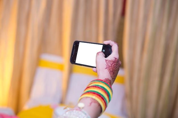 Menina tomando selfie segurando o telefone com bengals
