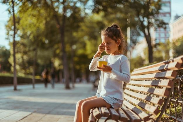 Menina tomando sorvete no parque