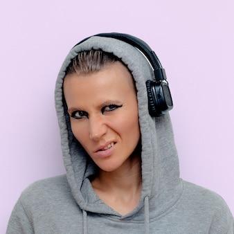 Menina tomboy em fones de ouvido elegantes. vibrações de dj de discoteca
