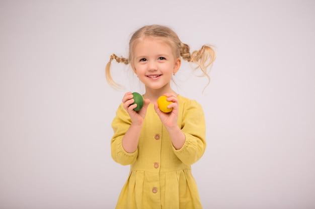 Menina tooddler juggles ovos e felizmente sorrisos