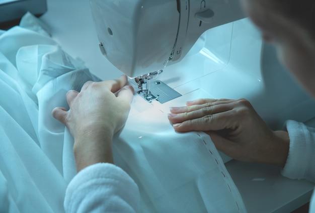 Menina trabalha em uma máquina de costura