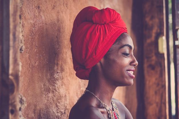 Menina tradicional de beleza africana sorrindo e olhando - lindo retrato para uma mulher bonita de pele negra - vestido tradicional e pele nua - rosto atraente de senhora afro com parede rural