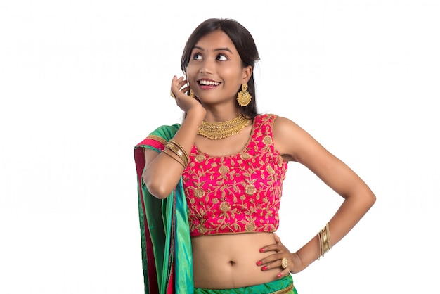 Menina tradicional indiana bonita posando no fundo branco.
