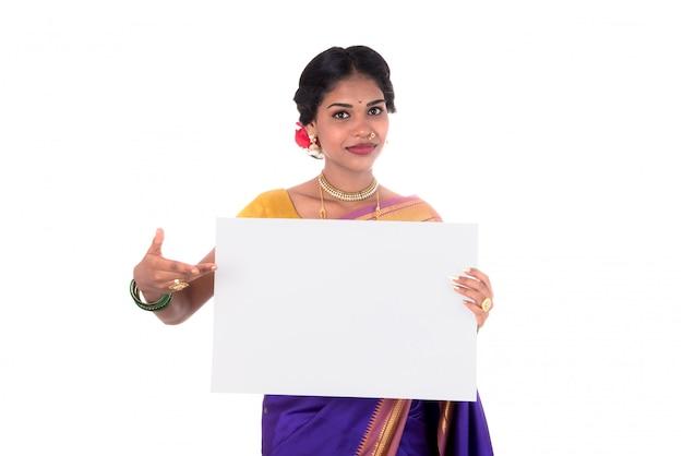 Menina tradicional, segurando e mostrando a placa branca em branco