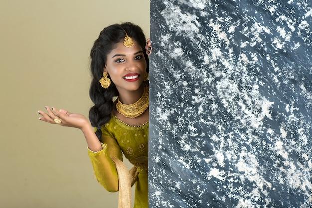 Menina tradicional segurando e mostrando placa texturizada