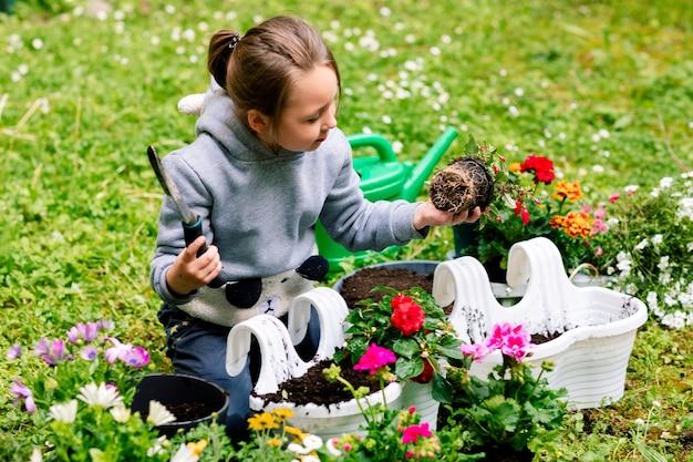 Menina transplantando flores em vasos para varanda no quintal.