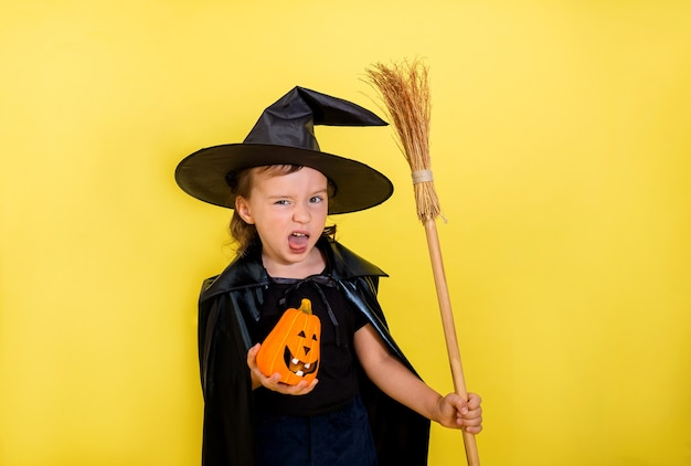 Menina travessa em um terno bruxas com um chapéu com uma abóbora e uma vassoura em uma parede amarela isolada com espaço para texto