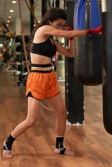 Menina treinando com saco de pancadas, preparando-se para uma luta