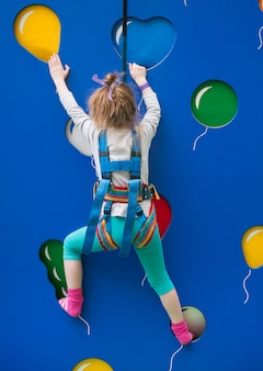 Menina treinando na parede de escalada