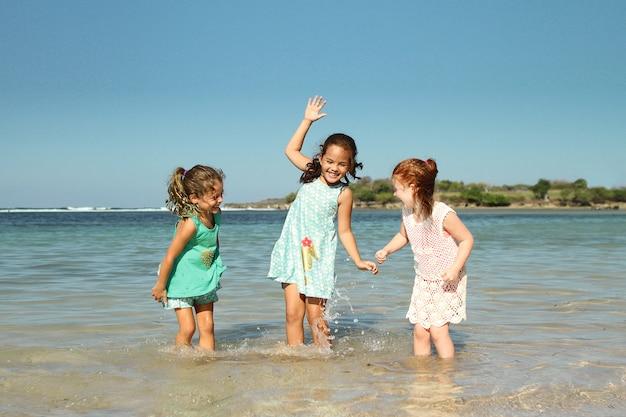 Menina três brincar na praia sob o céu azul de verão