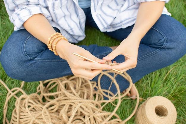 Menina tricota uma cesta de crochê na grama, sentada no jardim na grama. hobby em casa.