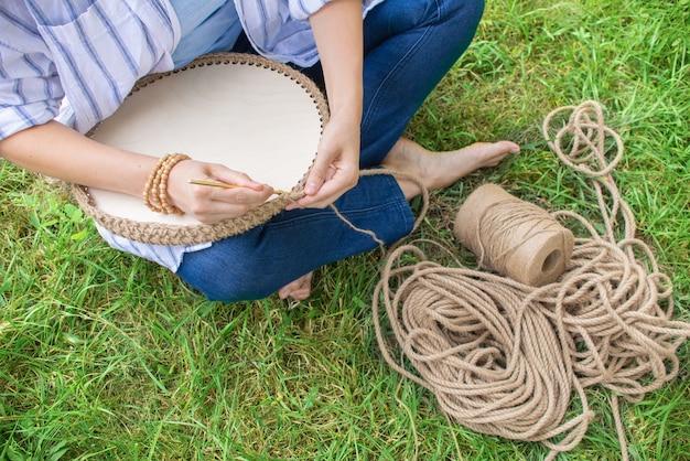 Menina tricota uma cesta de crochê na grama, sentada no jardim na grama. mulheres como passatempo em casa.