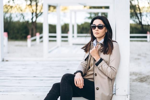 Menina triguenha do cabelo consideravelmente longo nos óculos de sol que relaxam ao ar livre.