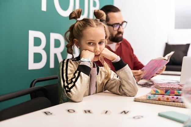 Menina triste. adorável garota de cabelos louros com pulseiras na mão, parecendo triste enquanto está sentada à mesa