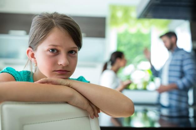 Menina triste, apoiando-se na cadeira enquanto os pais discutindo