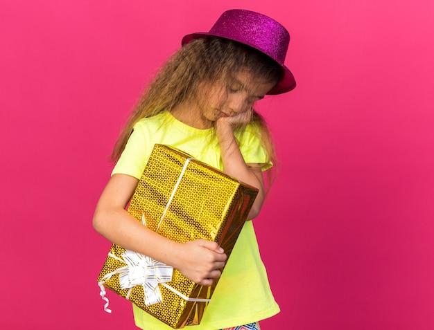 Menina triste caucasiana com chapéu de festa roxo, colocando a mão no rosto e segurando uma caixa de presente isolada na parede rosa com espaço de cópia