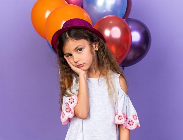 Menina triste caucasiana com chapéu de festa violeta, colocando a mão no rosto em frente a balões de hélio isolados na parede roxa com espaço de cópia