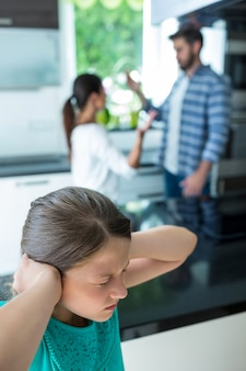 Menina triste, cobrindo os ouvidos enquanto os pais discutindo