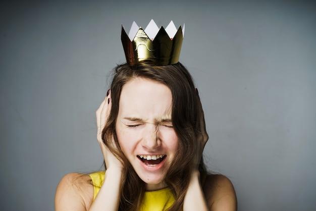 Menina triste com raiva em um vestido amarelo cobrindo as orelhas com as mãos, grita, na cabeça uma coroa de ouro