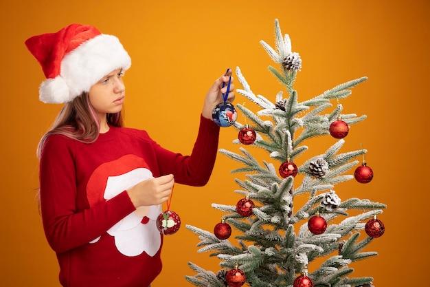 Menina triste com suéter de natal e chapéu de papai noel pendurando bolas em uma árvore de natal e parecendo infeliz sobre um fundo laranja