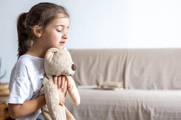 Menina triste com ursinho de pelúcia em casa no espaço da cópia de fundo desfocado.