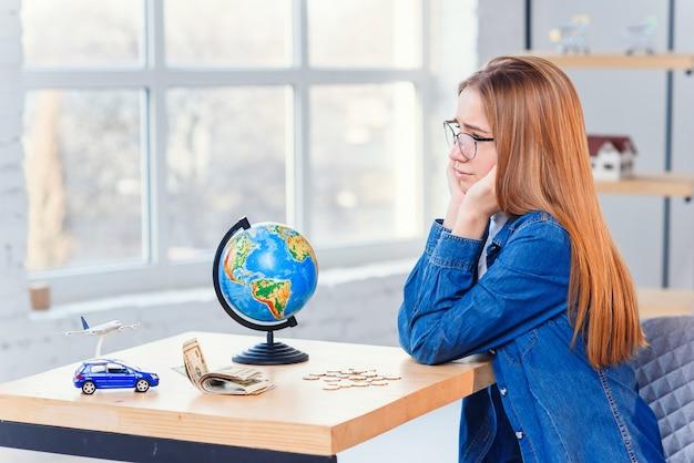 Menina triste conta suas economias e sonha com viagens e veículos próprios. conceito de dinheiro de poupança.