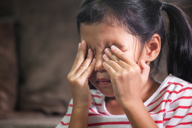 Menina triste criança asiática está chorando e esfregando os olhos com as mãos