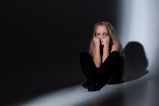Menina triste e assustada com olhos injetados de sangue e machucados chorando de medo.