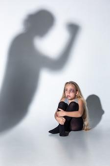 Menina triste e assustada com olhos injetados de sangue, machucados, chorando de medo da sombra na parede.
