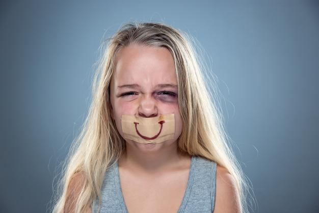 Menina triste e assustada com olhos vermelhos e machucados e sorriso falso na boca.