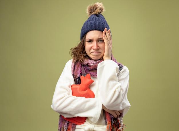 Menina triste e doente vestindo túnica branca e chapéu de inverno com lenço segurando uma bolsa de água quente, colocando a mão na cabeça isolada em verde oliva