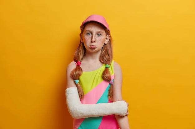 Menina triste e sardenta e sombria usa maiô e boné coloridos, braço quebrado engessado, férias estragadas por causa do trauma, isolado sobre parede amarela. horário de verão, crianças, conceito de acidente