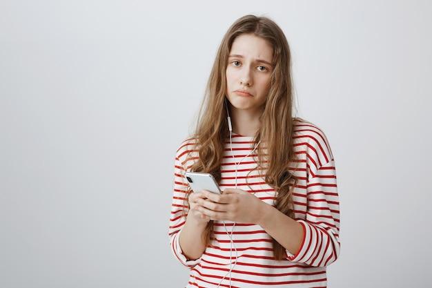 Menina triste e triste parecendo aflita ao usar o telefone celular e fones de ouvido