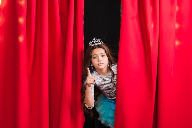 Menina triste em pé atrás da cortina vermelha gesticulando