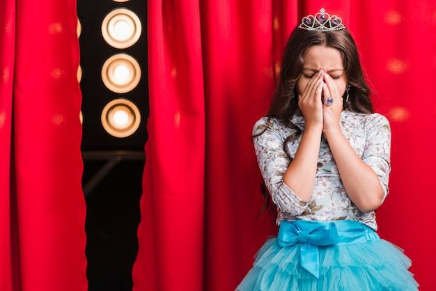 Menina triste em pé atrás da cortina vermelha
