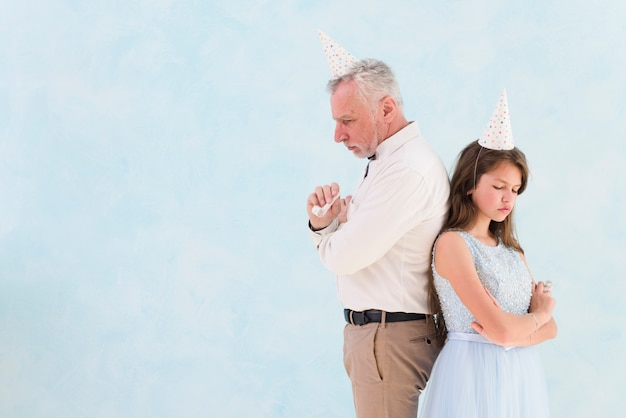 Menina triste em pé atrás de seu avô contra o fundo azul