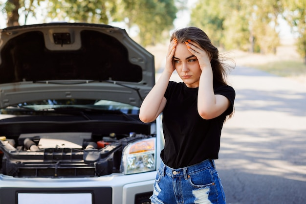 Menina triste em pé perto do carro com o capô aberto