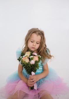 Menina triste em um vestido festivo com um buquê de flores frescas em um fundo branco