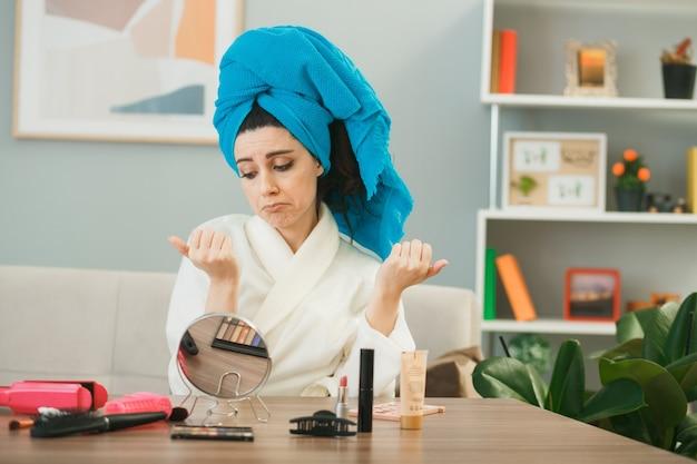 Menina triste enrolada em uma toalha de cabelo com unhas de gel secas, sentada à mesa com ferramentas de maquiagem na sala de estar