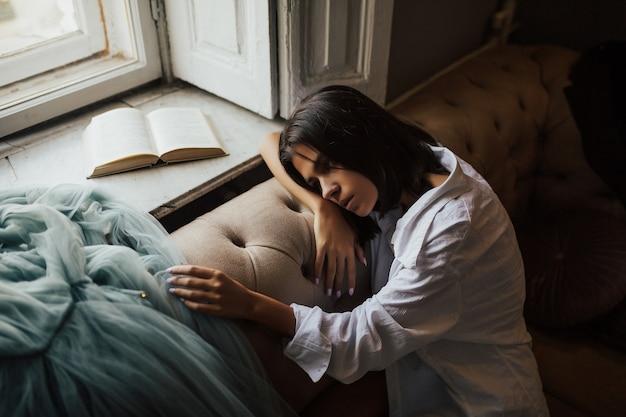 Menina triste no sofá perto da janela, olhando para baixo. mulher jovem deprimida perto da janela de casa