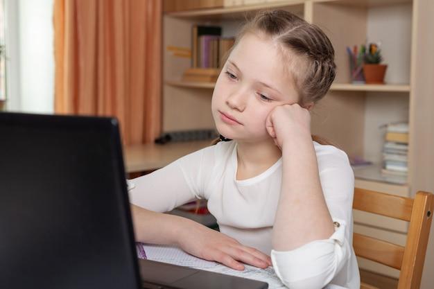 Menina triste olha para uma tela de laptop. educação on-line a distância, escola em casa, educação em casa,